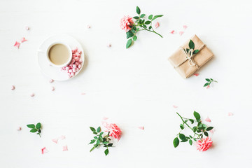 Workspace. Gift, cup of coffee and rose flowers. Flat lay, top view