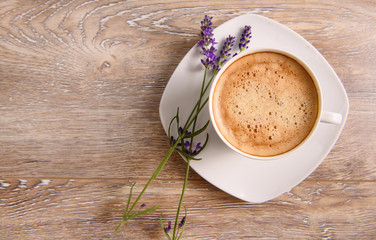 A cup of coffee on wooden background with lavenders top view. Good morning background with copy space