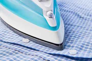 Closeup view of  modern iron on blue shirt