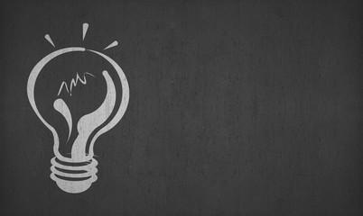 hand drawing light bulb on left side blackboard or chalkboard