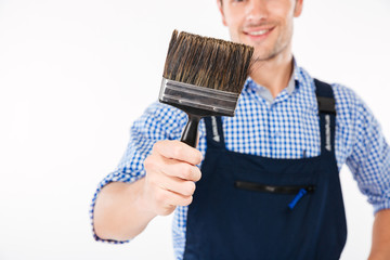 Cropped image of smiling male builder holding paint brush