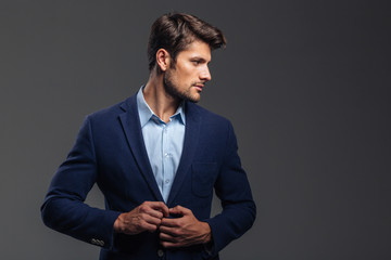 Portrait of a man buttoning his jacket and looking away