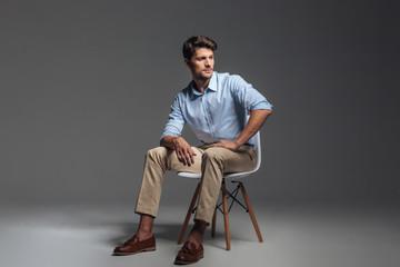 Fototapeta Pensive brunette man in blue shirt sitting on the chair