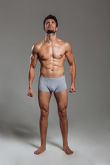Handsome sexy athletic man in underwear posing and looking up