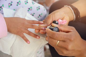 Woman applying nail polish, doing manicure to a little girl, fun activity at home or girl birthday party