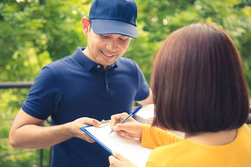 Smiling delivery man deliver parcel box to a woman