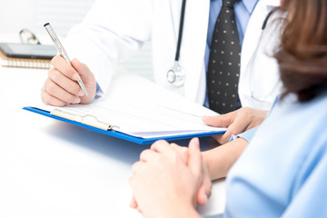 Doctor talking note on clipboard while consulting with woman patient