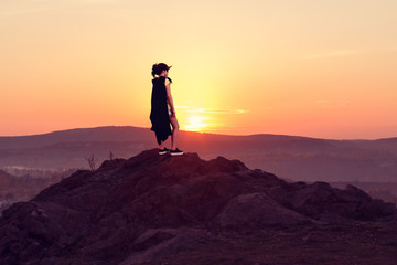 Girl super hero is on top of a mountain at sunset gazing into the distance.