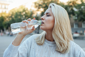 Young woman is drinking water from plastic bottle. City backgrou