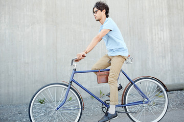 young hipster man riding fixed gear bike