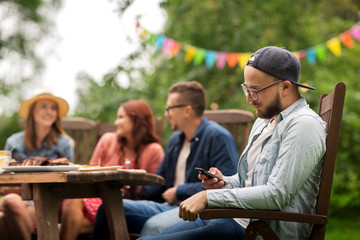 man with smartphone and friends at summer party