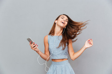 Happy carefree woman dancing and listening to music from smartphone