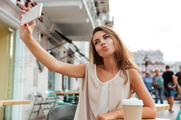 Beautiful young woman taking selfie with smartphone sitting in cafe