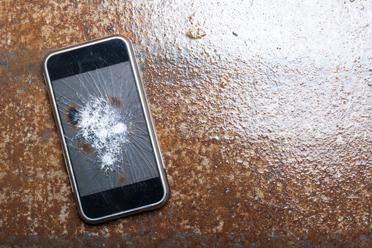Broken Phone with cracked screen on metal background