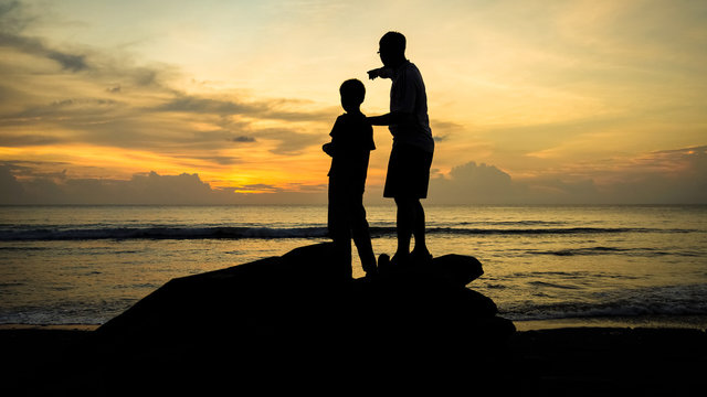 Father & Son Bonding and Pointing to the Horizon During an Orange Beach Sunset