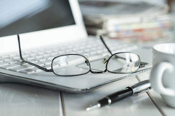 Eyeglasses on laptop and coffee