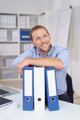 mann im büro stützt sich auf aktenordner und schaut lächelnd nach oben