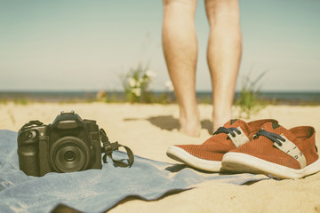 Camera with lens lying a towel on the sand at the beach, standing beside red shoes, and in the background can be seen the feet of the photographer, looking at the sea