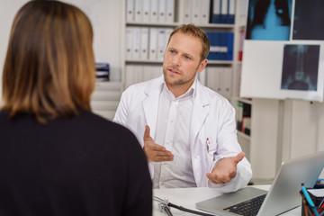 arzt erklärt einer patientin etwas in der praxis