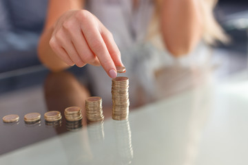 Woman hands build coin columns closeup