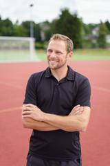 lächelnder mann steht mit verschränkten armen auf dem sportplatz