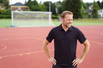 mann steht draußen auf einem sportplatz