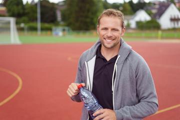 sportler steht auf dem sportplatz mit einer flasche wasser