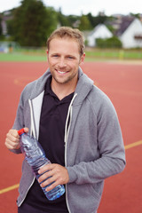 sportler mit einer flasche wasser steht draußen auf dem sportplatz