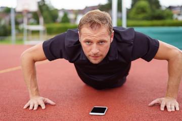 mann trainiert draußen auf dem sportplatz mit einer app