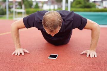 sportler macht liegestütz und schaut auf sein handy