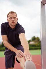 sportler dehnt seine wade vor dem training