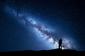 Milky Way. Night landscape with silhouettes of hugging and kissing man and woman on the mountain. Sky with stars. Silhouette of lovers. Couple, relationship. Blue milky way with people. Universe