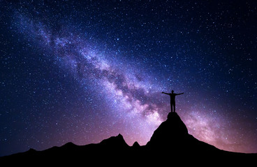 Milky Way. Silhouette of a standing man with raised up arms on the top of mountain. High rocks, mountain peak. Beautiful galaxy. Universe. Blue night starry sky. Night landscape with purple milky way