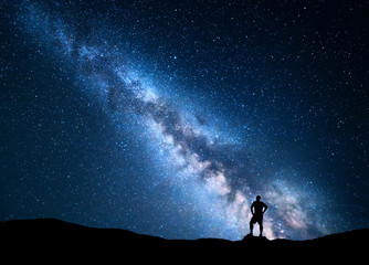 Milky Way. Beautiful night sky with stars and silhouette of a standing man on the mountain. Blue milky way with man on the hill. Background with galaxy. Silhouette of a man. Universe. Night landscape