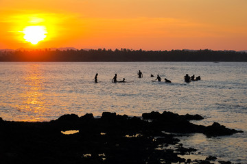 Surfers Waiting For Waves in the Water During Orange Siargao Island Sunset - Philippines
