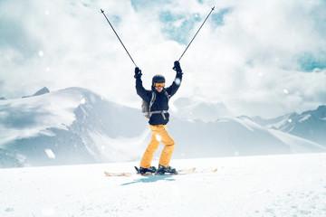 Glücklicher Skifahrer streckt die Skistöcke in die Luft