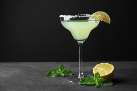 Delicious cocktail with lime slice and mint on gray table