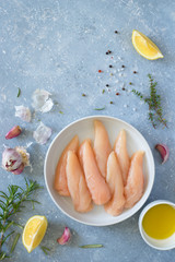 Fresh raw chicken tenders, lemon, garlic, rosemary, olive oil, pepper and salt