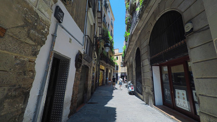 BARCELONA CATALONIA SPAIN - JULY 2016: Smooth camera steady shot along narrow street in the center of barcelona, near to gothic quarter, clear blue sky with sun shining, tourists slowly walking along