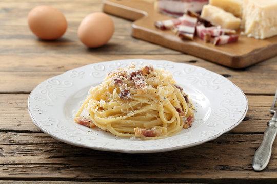 pasta carbonara  con uova carne e formaggio sfondo tavolo di cucina rustico