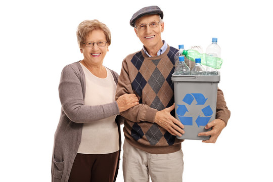 Mature couple posing with a recycling bin