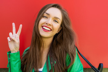 Beautiful smiling brunette woman over red background showing a p
