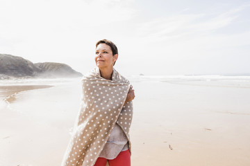 Mature woman wrapped in a blanket on the beach