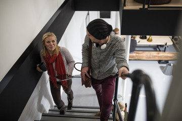 Young woman and man with headphones walking up stairs