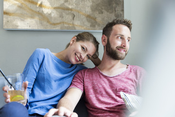 Smiling young couple sitting on couch with drink