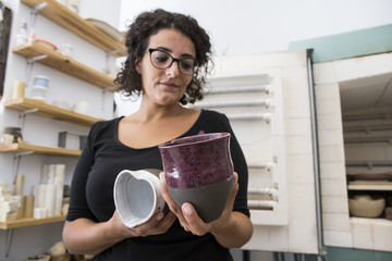 Woman examining cups of ceramic in a workshop