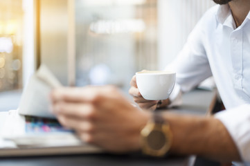 Close-up of businessman with cup of coffee reading newspaper in a cafe