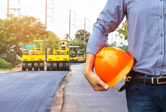 engineer holding safety helmet at road construction site with roller compactor working asphalt road