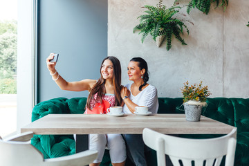Two women making selfie in a cafe