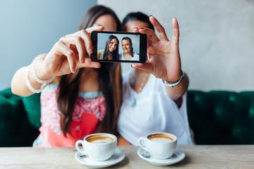 Two women making selfie in a cafe